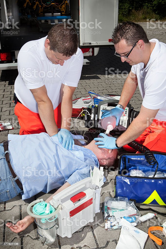 Medical emergency. Two male paramedics treating an unconscious victim...
