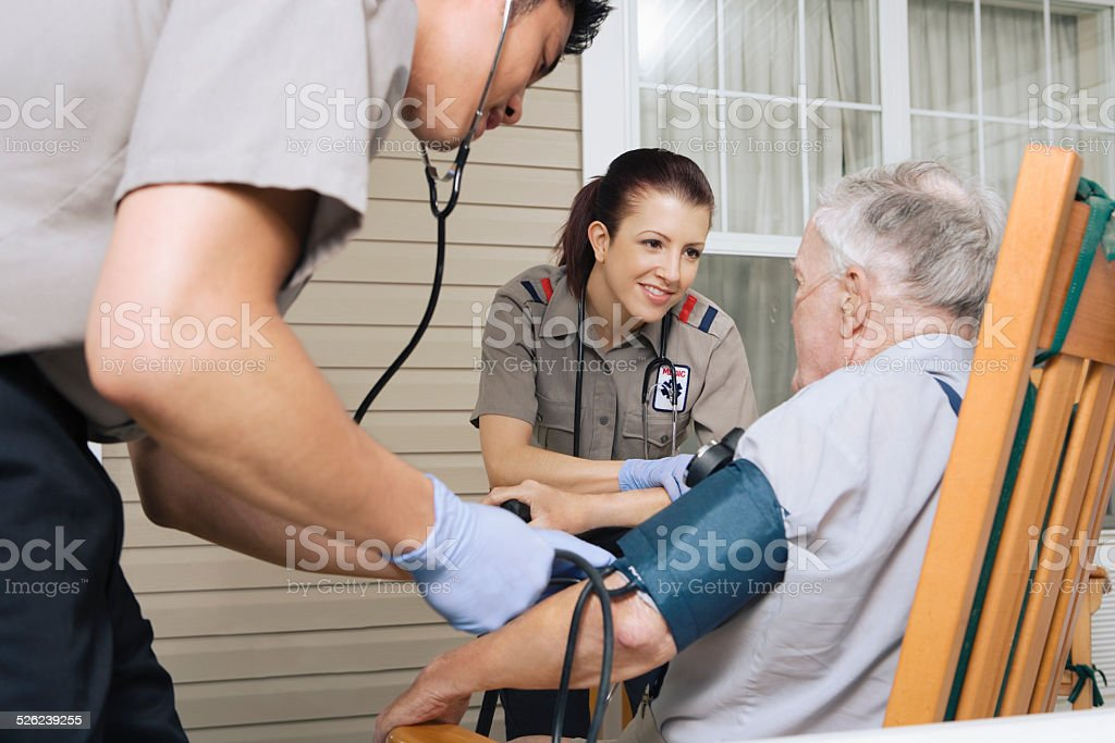 Paramedics examining senior man on porch stock photo