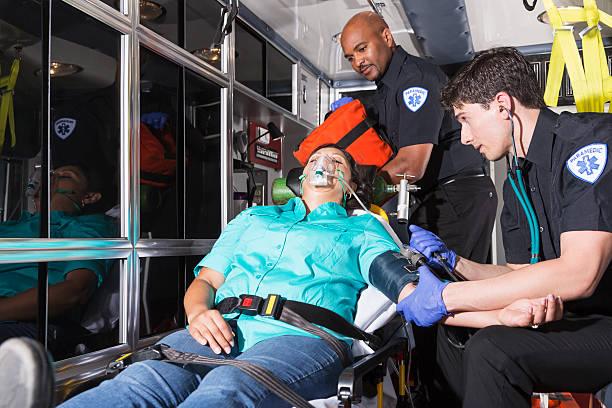 auxiliaires médicaux aider un patient - auxiliaire médical photos et images de collection