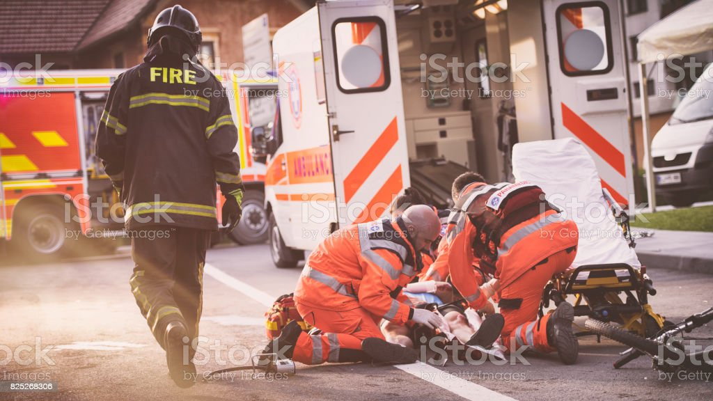 Paramedics helping injured cyclist stock photo
