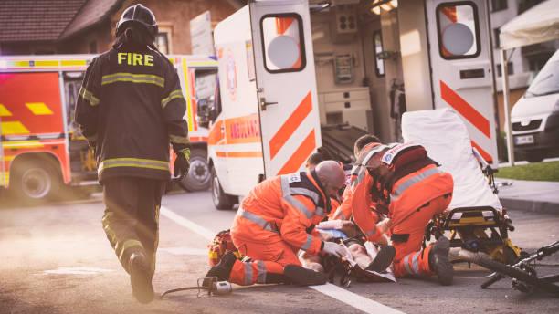 auxiliaires médicaux aident blessé cycliste - auxiliaire médical photos et images de collection