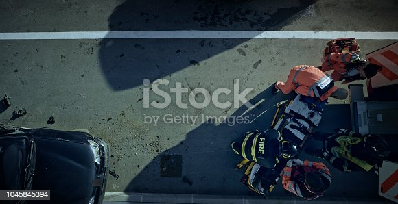 istock Paramedics lifting injured man on stretcher and preparing him for transport 1045845394