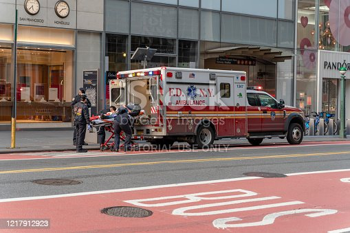 Manhattan, New York, USA - April 6, 2020: Paramedics loading a patient into the ambulance on 42 Street in Midtown Manhattan deserted because of the COVID-19 outbreak.