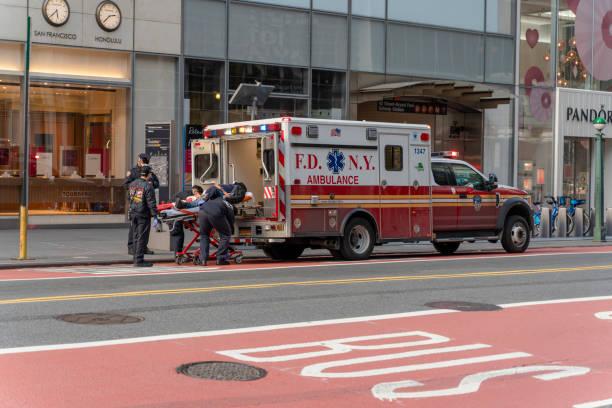 Sanitäter laden einen Patienten in den Krankenwagen auf der 42 Street in Midtown Manhattan. – Foto