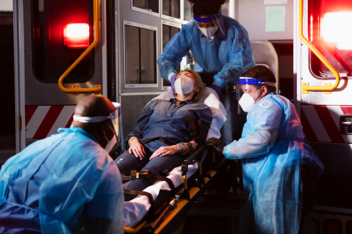 A mature woman in her 40s lying on a stretcher being loaded into an ambulance by three paramedics providing emergency medical care. The EMTs are wearing PPE, including gowns, face shields and masks. They are working during the COVID-19 pandemic, trying to protect themselves from catching and spreading coronavirus.