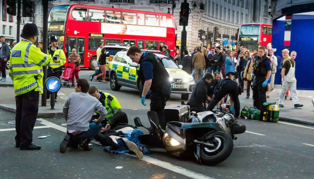 paramedics provide first aid to victims in a motorcycle accident. london - emergency response stock pictures, royalty-free photos & images