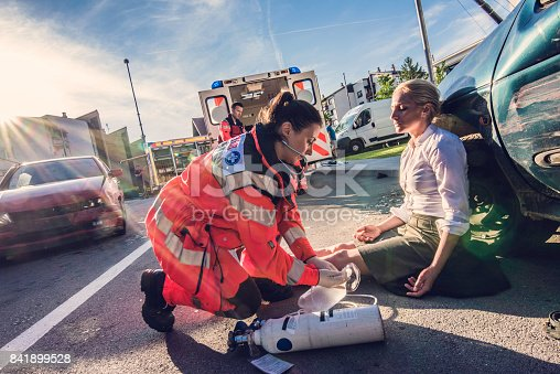 Female doctor providing first aid to woman injured in car accident.