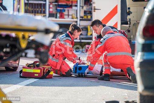 Paramedics providing first aid to man injured in car accident.