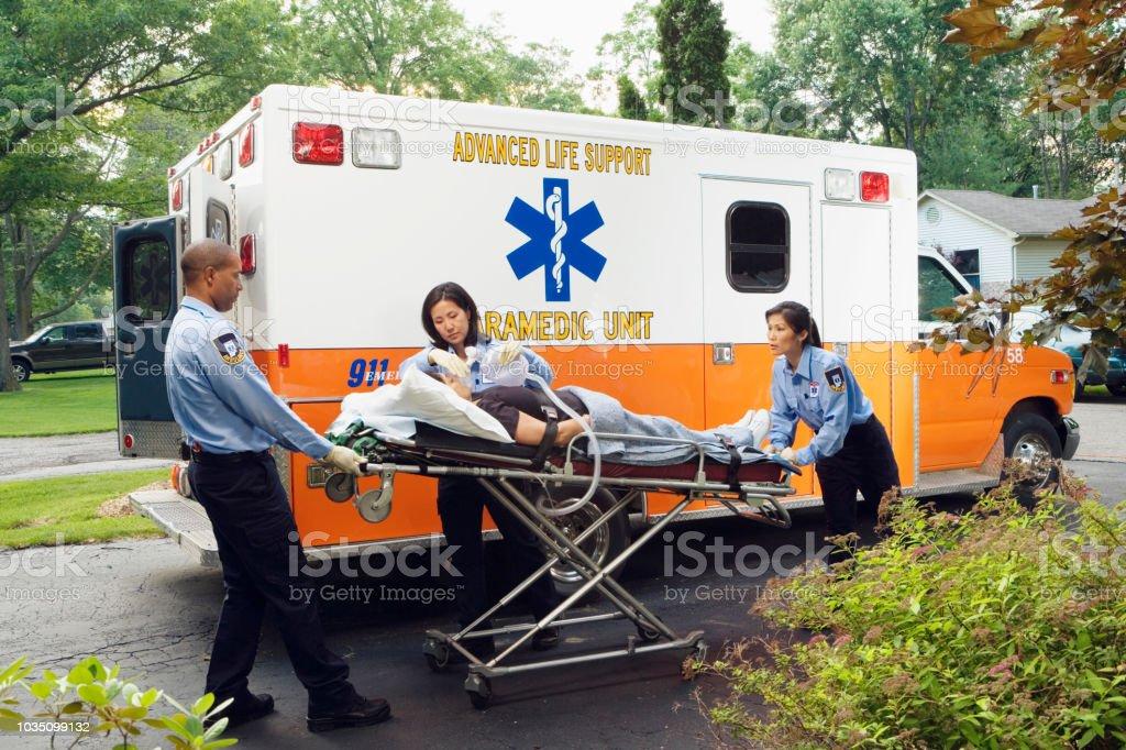 Paramedics putting woman into ambulance