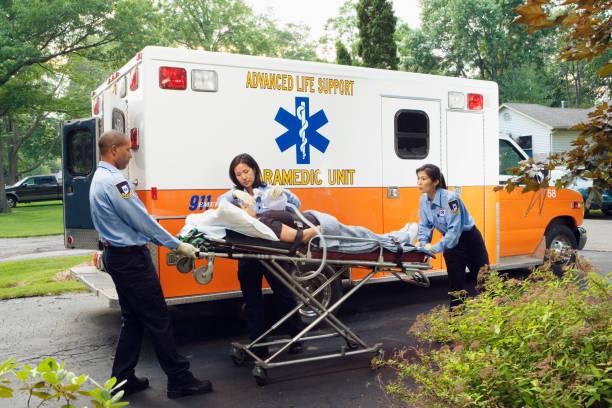 ambulanciers paramédicaux mettant la femme en ambulance - auxiliaire médical photos et images de collection