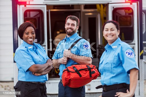 A multi-ethnic group of three paramedics standing at the rear of an ambulance, in front of the open doors . The focus is on the young man in the middle, carrying a medical trauma bag. They are looking at the camera, smiling.