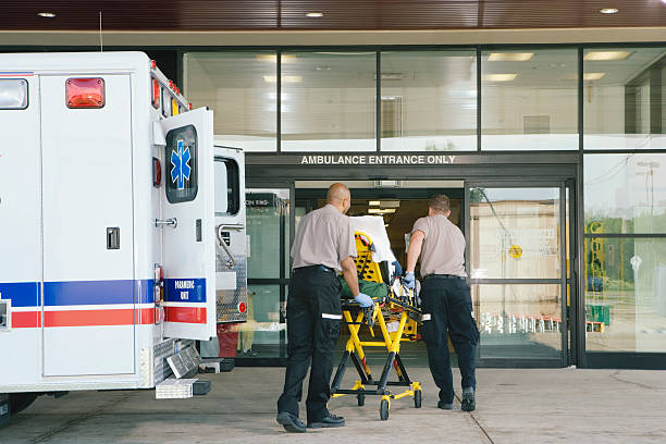 paramedics taking patient on stretcher from ambulance to hospital - entrance stock photos and pictures