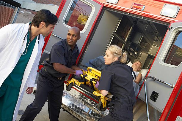 paramedics unloading patient from ambulance - ambulance stock photos and pictures