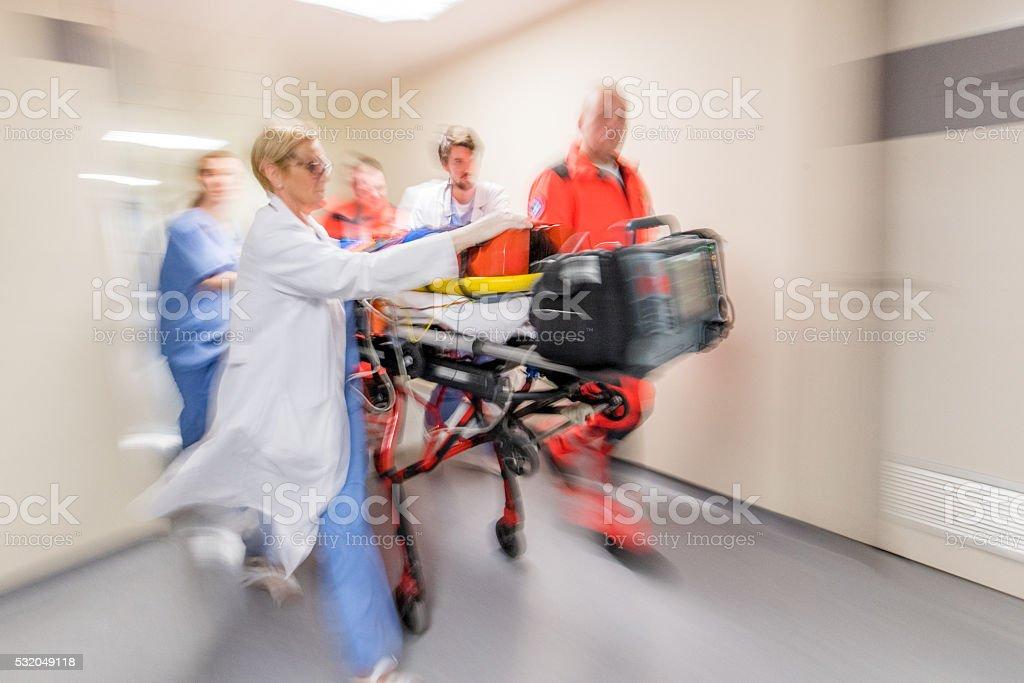Paramedics wheeling patient in hospital stock photo