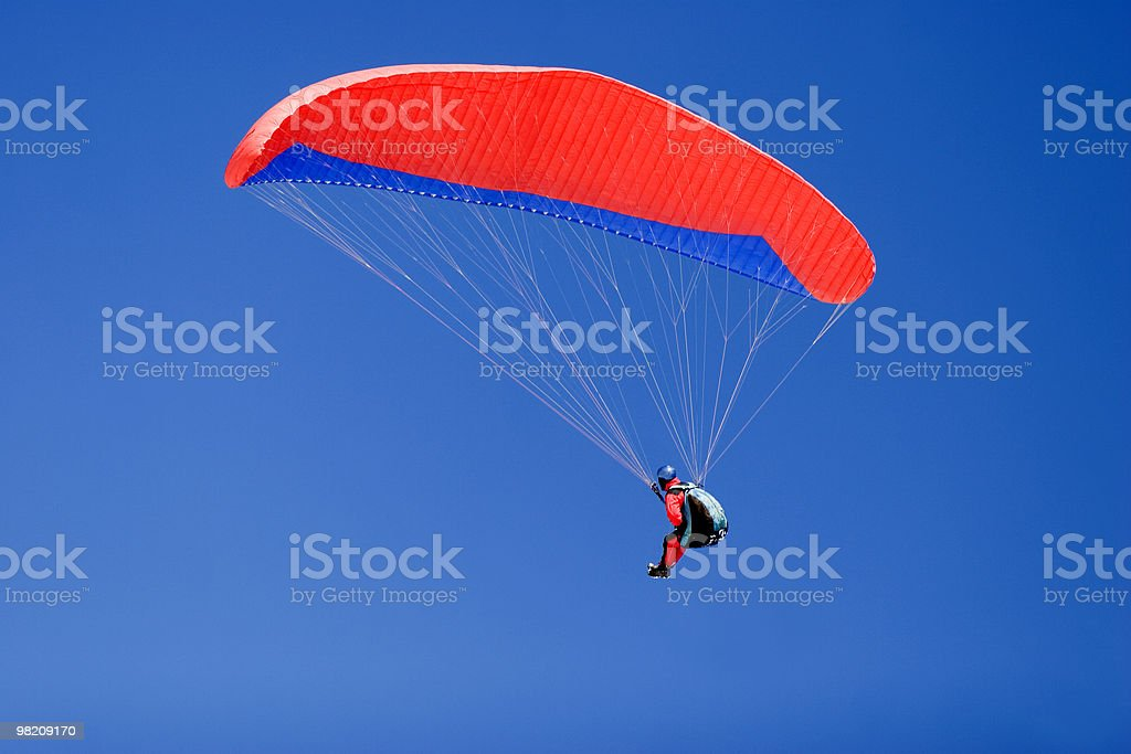 paraplane flying high up in the deep blue sky stock photo