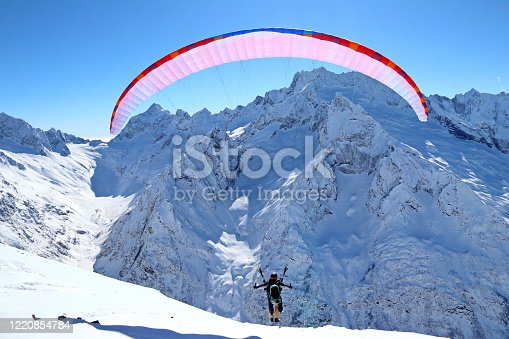 paraplane flying over snowy Caucasus mountains and sunny blue sky