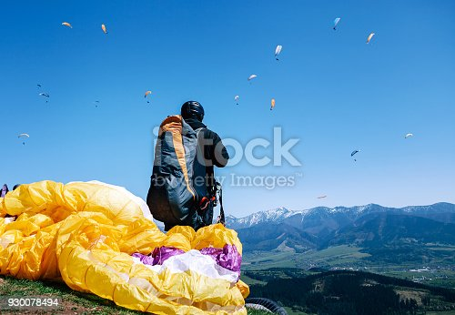 istock Paraplanner in full equipment for flight looks on soaring another paraplanes in sky 930078494