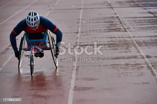 istock Paraplegic male athlete in racing wheelchair warming up alone outdoors 1219932531