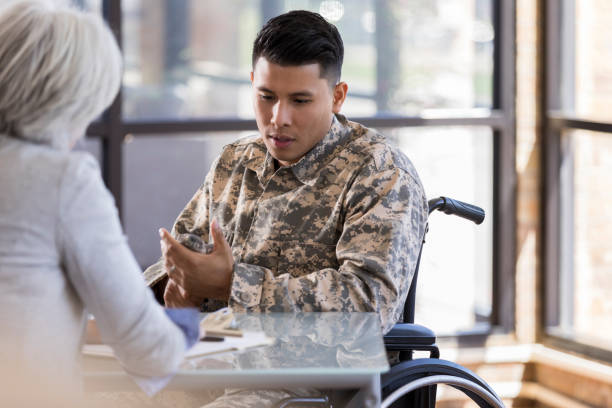 Paraplegic soldier talks with female therapist Vulnerable wheelchair-bound male soldier with PTSD discusses hard issues with a caring female mental health professional. paraplegic stock pictures, royalty-free photos & images