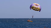 Parasailing water amusement - flying on a parachute behind a boat on a summer holiday.  Tourist with parasailing on ocean sea with blue sky background.