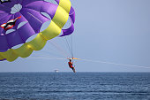 Kusadasi, Turkey​ -​ September 2020: Man with action camera flying on parachute near the Kusadasi coast in Turkey
