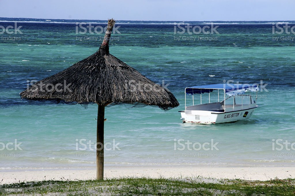Parasol and glass bottom boat at the coastline of mauritius stock photo