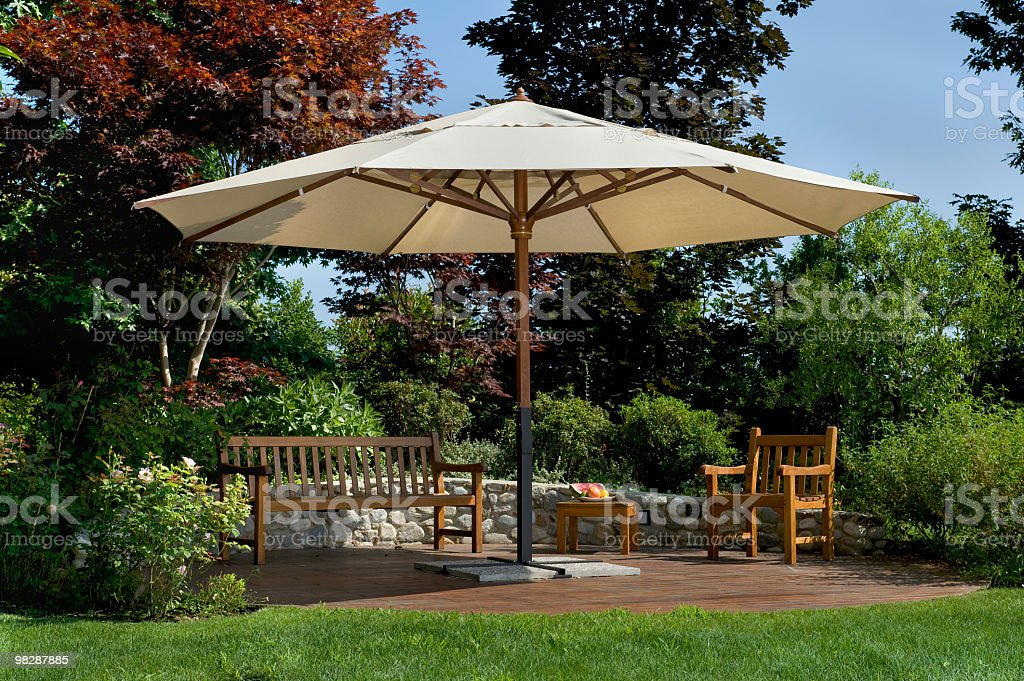 Parasol in a garden with wooden bench and chairs royalty-free stock photo