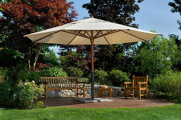 Parasol in a garden with wooden bench and chairs stock photo
