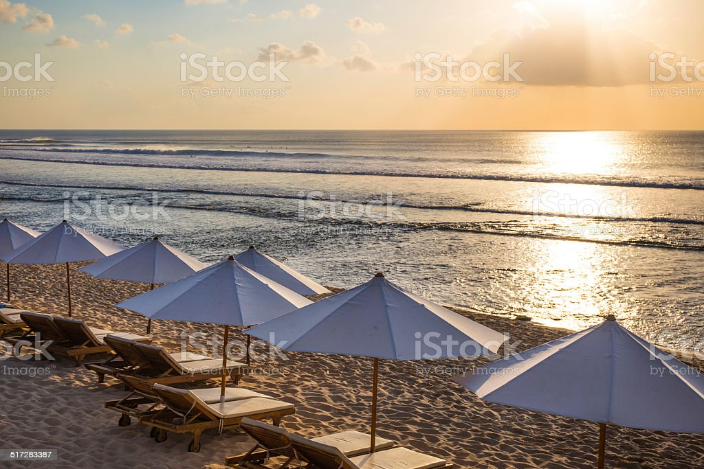 Parasols and deckchairs on the beach at sunset stock photo