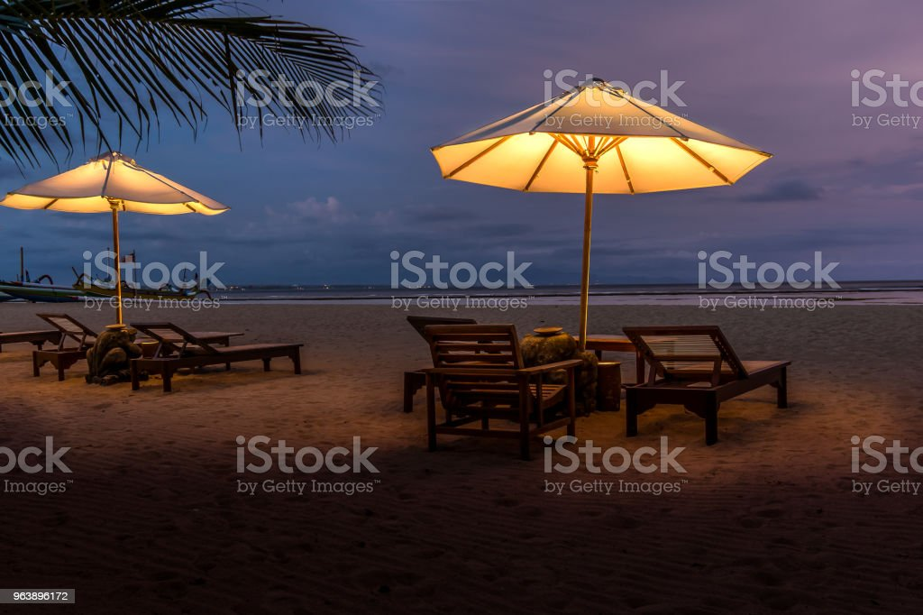 Parasols and sunbeds on a tropical beach  at night - Royalty-free Bali Stock Photo