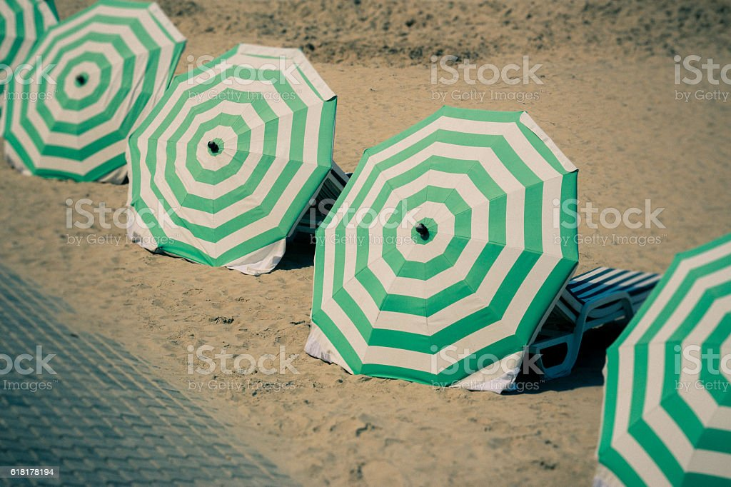 Parasols lined up on beach stock photo