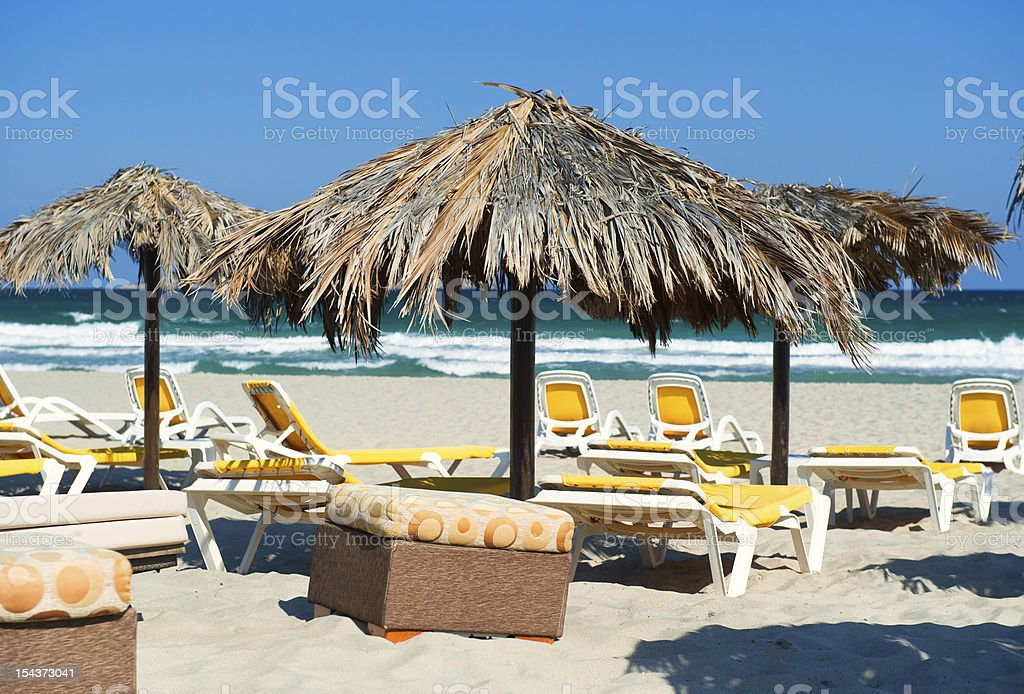 Parasols with deckchairs on the beach under blue sky stock photo
