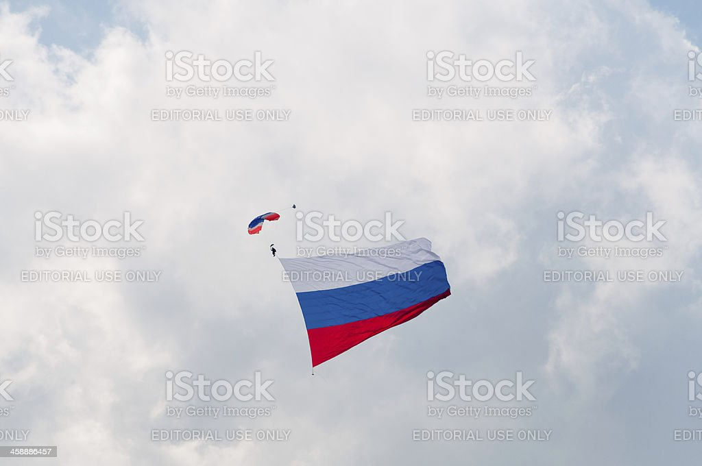 Paratrooper with giant Russian national flag against cloudy sky background royalty-free stock photo