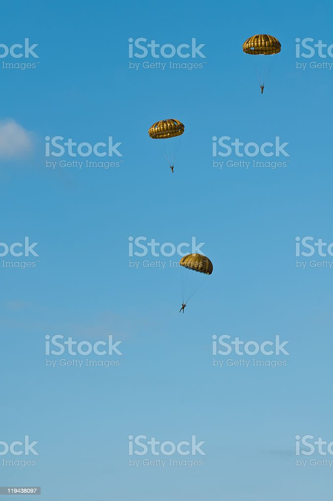 Paratroopers with golden parachutes stock photo