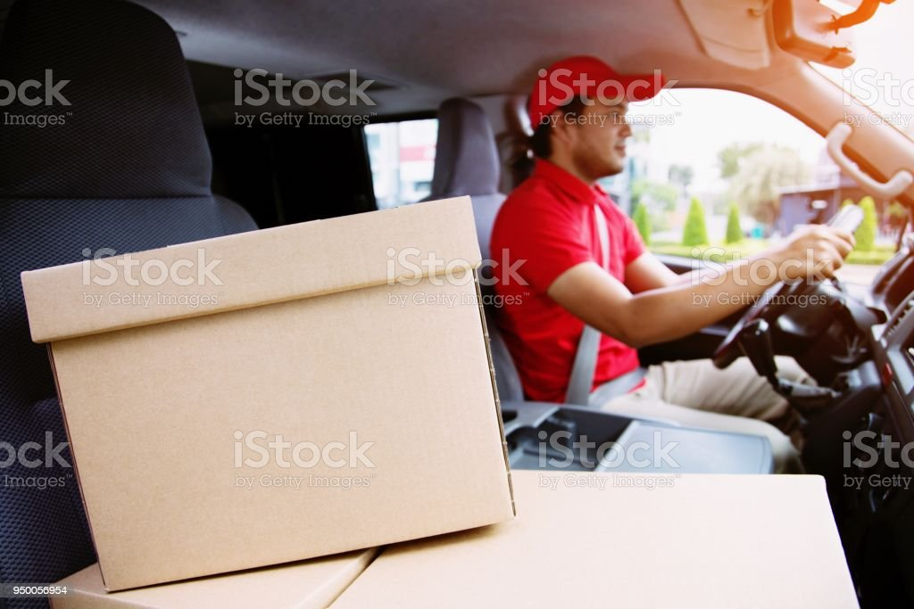parcel delivery man drive a car Smiling young male postal delivery...