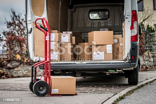 Stack of cardboard boxes and parcels in delivery van.