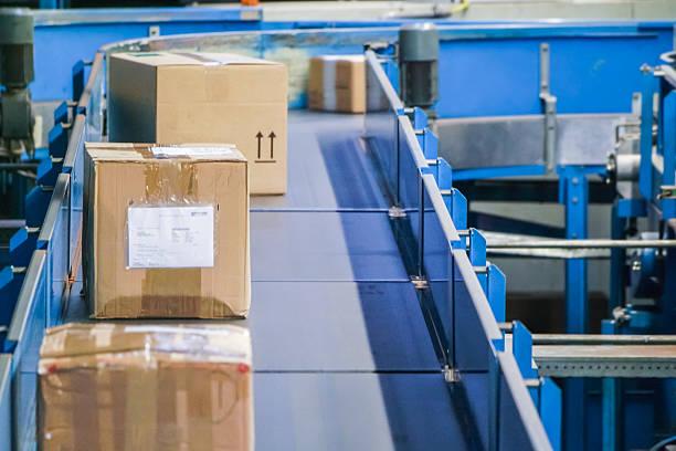 Pakete auf-Förderanlagen mit industriellen Hintergrund verschwommen – Foto