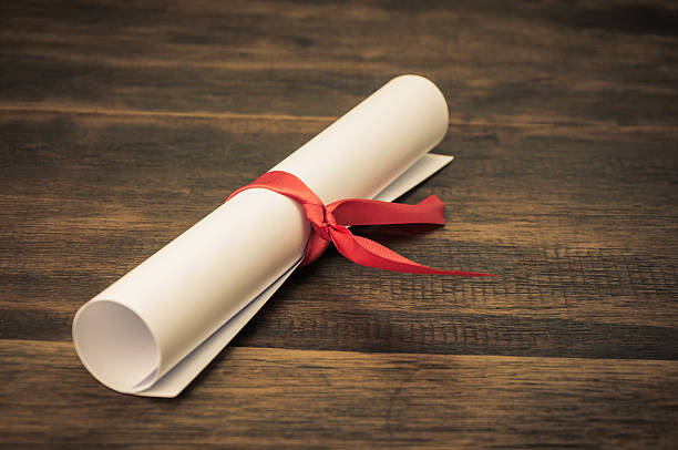 Parchment diploma scroll on wood background stock photo