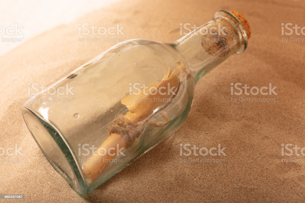 Parchment message in a bottle on the beach royalty-free stock photo
