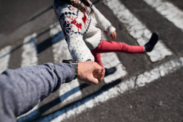 Parent and child across the crosswalk holding hands stock photo