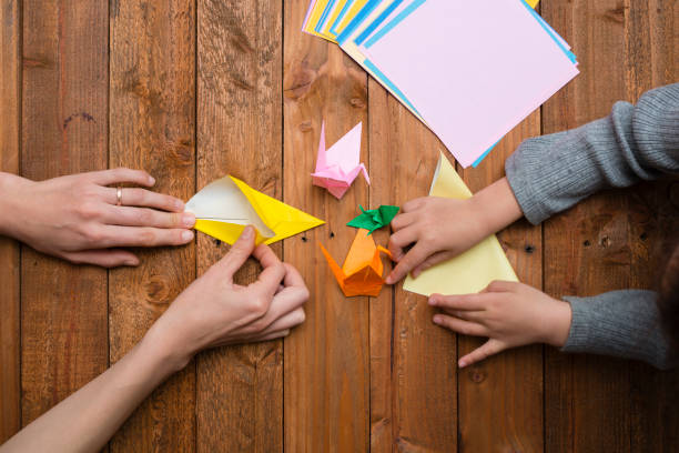 parent et enfant main jouant avec origami - origami photos et images de collection