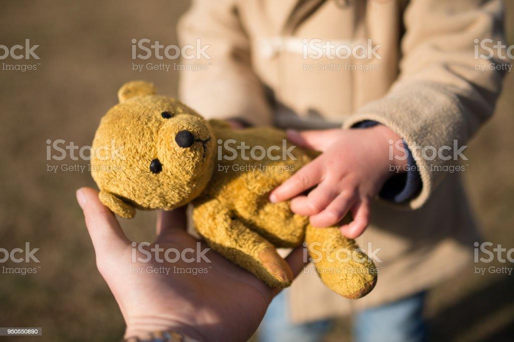 親と子のテディー ・ ベアを渡す ストックフォト