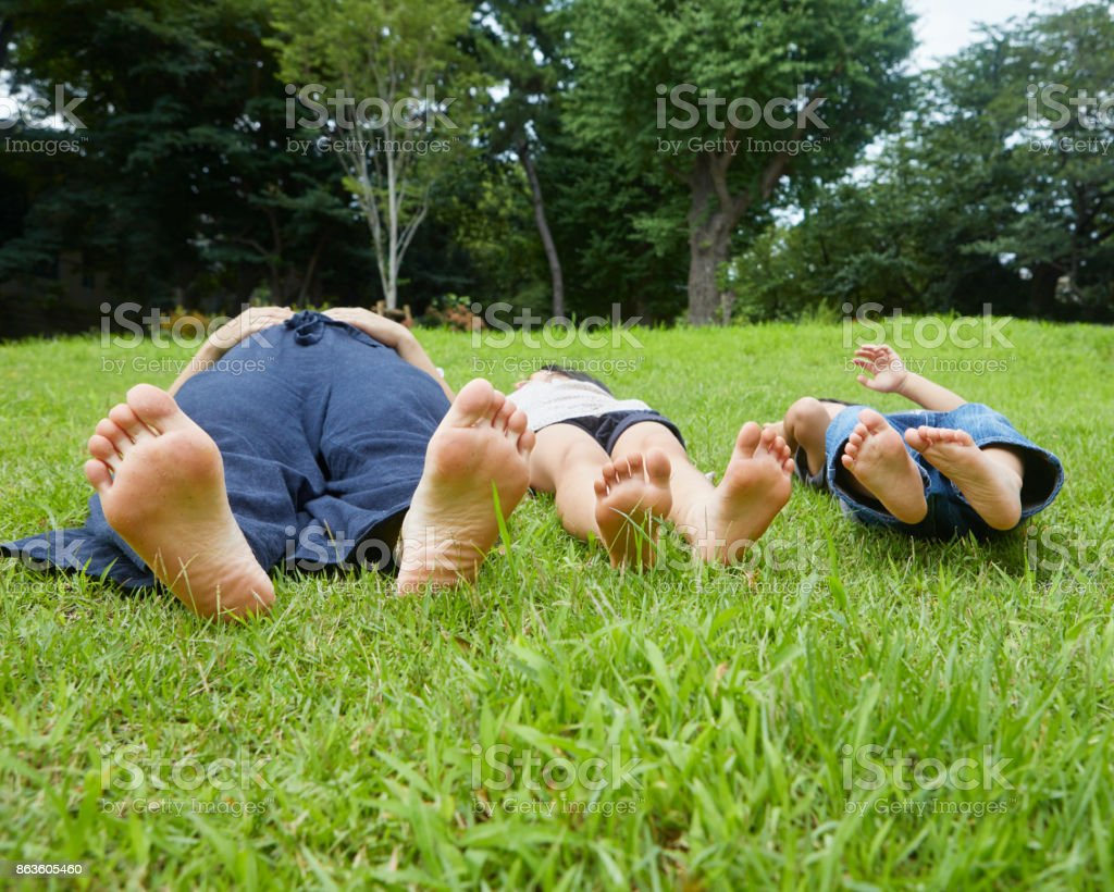 Parent and child lying on the grass stock photo