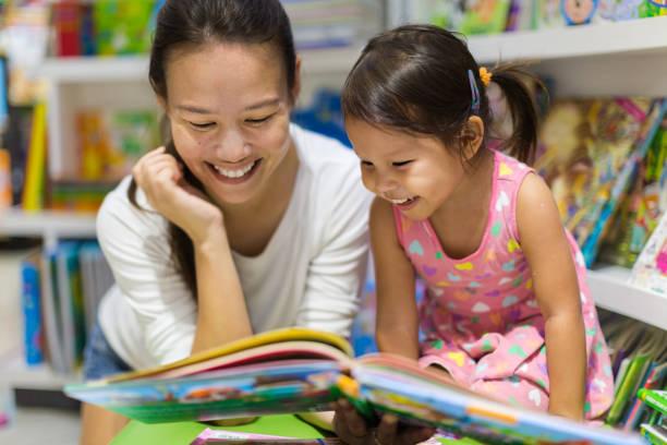 föräldrar och barn läser böcker tillsammans i biblioteket. - förälder bildbanksfoton och bilder