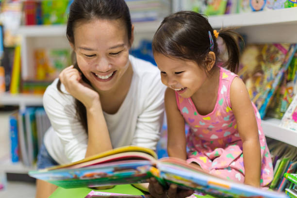 Parent and child reading books together in the library. Teacher reading a educational book to her female student, having a good time in class learning. preschool age stock pictures, royalty-free photos & images