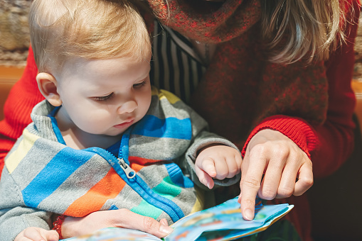 Parent and child reading books together in the library