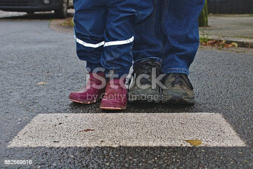 istock Parent and child waiting together at the cross walk, shown from the knee down 882569516