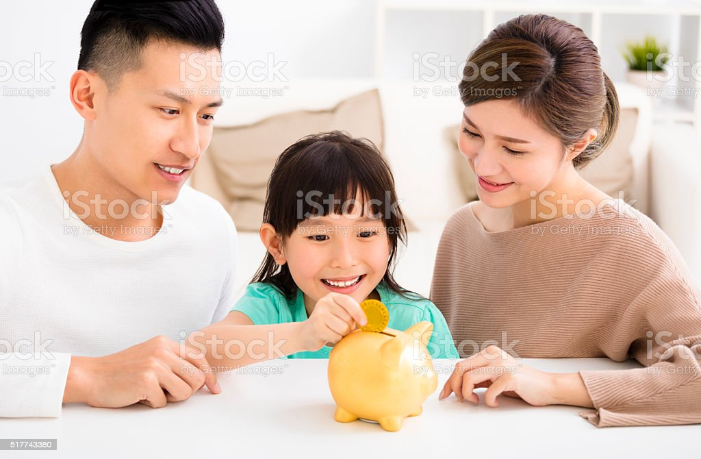 parent and daughter putting coins into piggy bank royalty-free stock photo