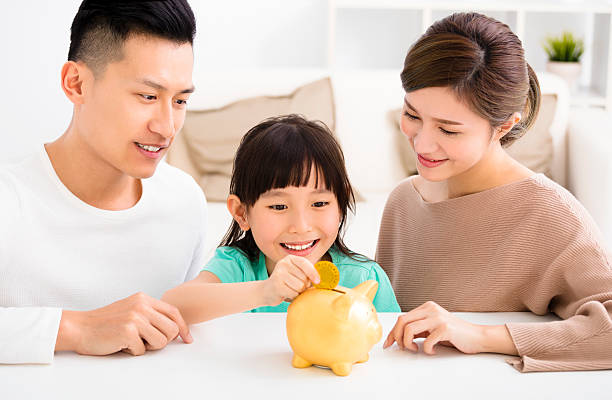 parent and daughter putting coins into piggy bank stock photo