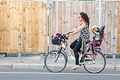 Berlin, Germany, 20 May 2018: parent and his little toddler daughter riding a bike at a city street